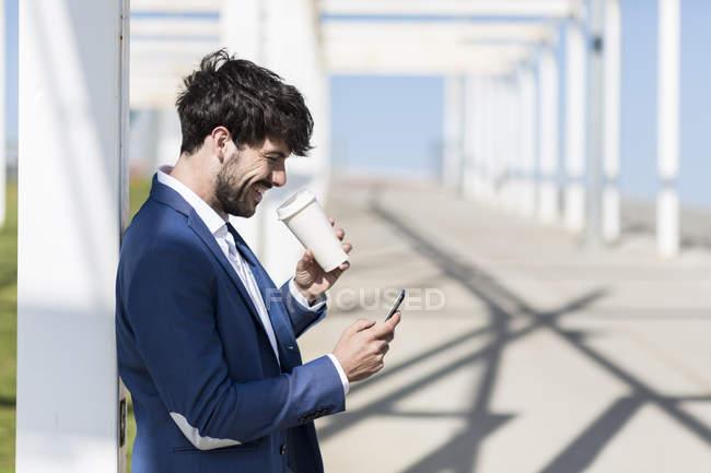 Empresário segurando smartphone e café takeaway — Fotografia de Stock
