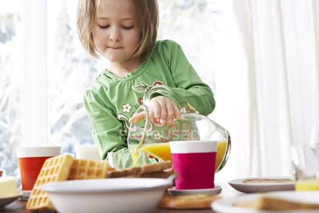 Girl pouring orange juice — Stock Photo