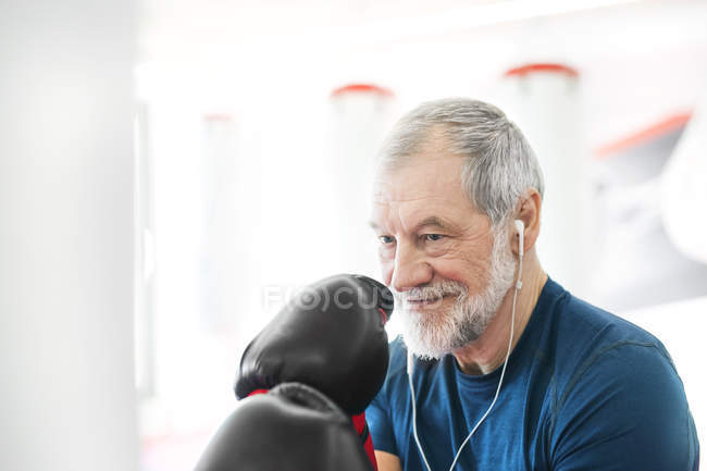 Senior man with earphones and boxing gloves — Stock Photo