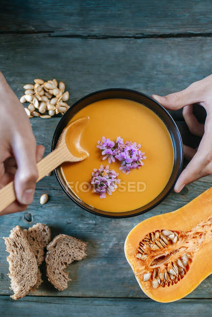 Male hands eating creamed pumpkin soup — Stock Photo