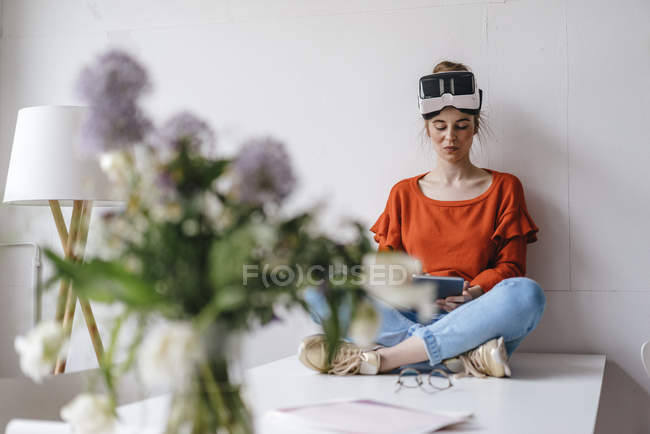 Woman sitting on table using tablet — Stock Photo