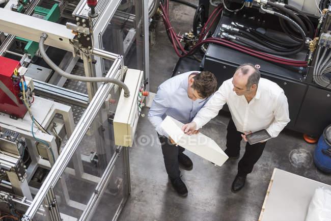 Men examining product in factory — Stock Photo