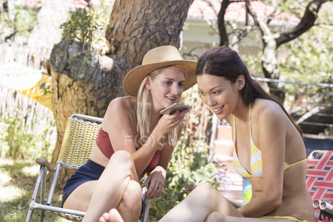Жінки в саду, спільного використання стільникового телефону — стокове фото