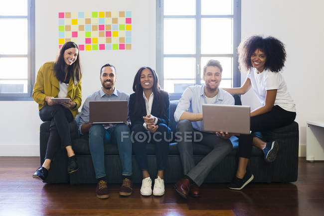 Colleagues sitting on couch with laptops — Stock Photo