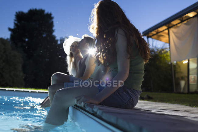 Friends sitting at poolside at evening — Stock Photo
