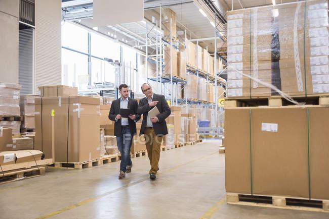 Deux hommes qui marchent dans l'entrepôt de l'usine — Photo de stock