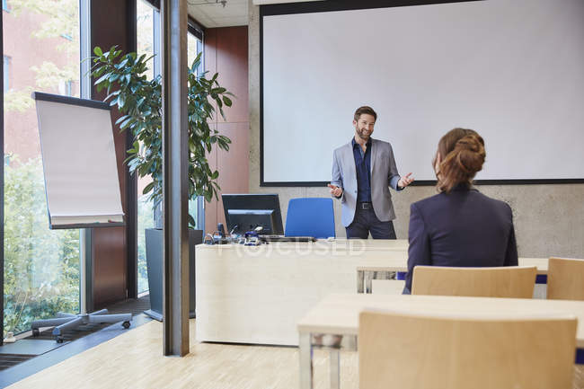 Coach talking to woman in training room — Stock Photo