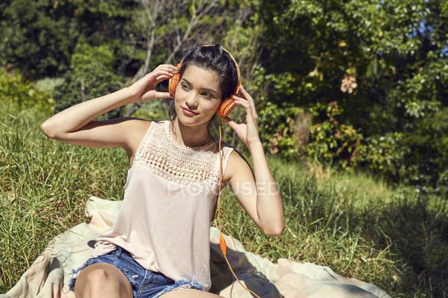 Женщина сидит на одеяле и слушает музыку в наушниках — стоковое фото