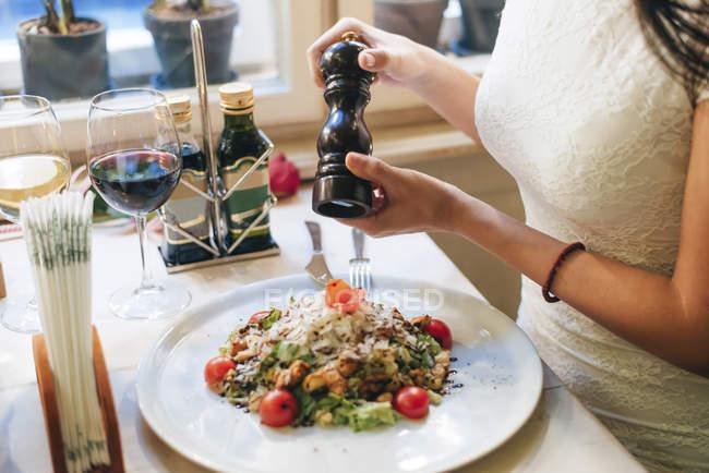 Woman salting dish at table — Stock Photo