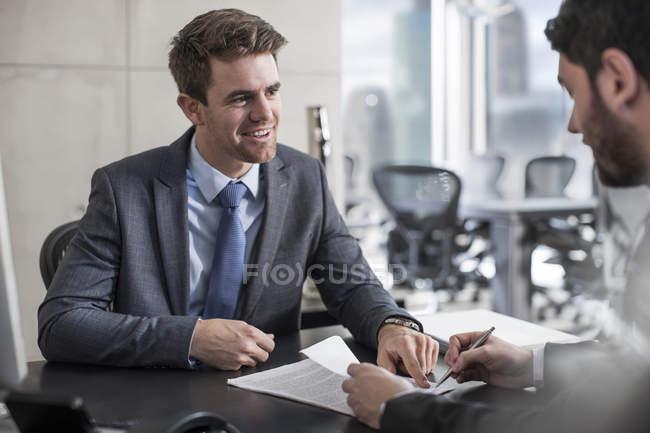 Businessman showing client document — Stock Photo