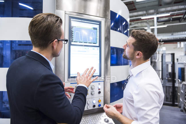 Men looking at screen in factory — Stock Photo