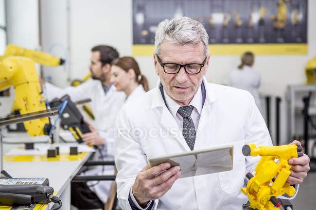 Engineer holding tablet and model of an industrial robot — Stock Photo