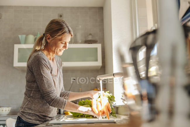 Woman in kitchen washing carrots — Stock Photo