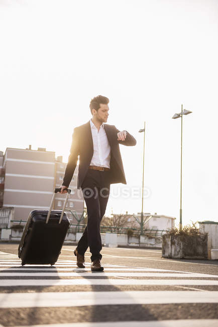 Businessman walking with rolling suitcase — Stock Photo