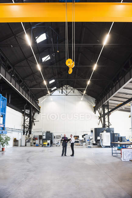 Businessmen standing on factory shop — Stock Photo