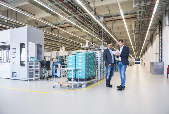Men discussing in factory — Stock Photo