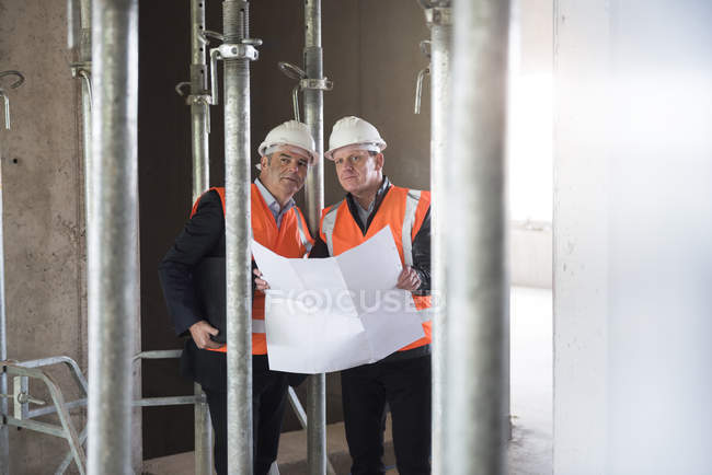 Men standing in building under construction — Stock Photo
