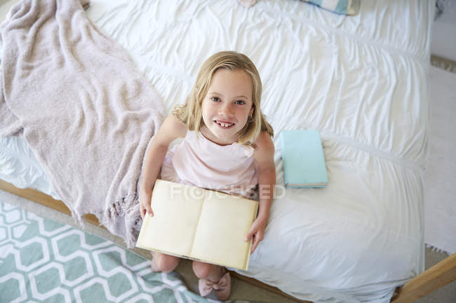 Girl sitting on bed with book — Stock Photo