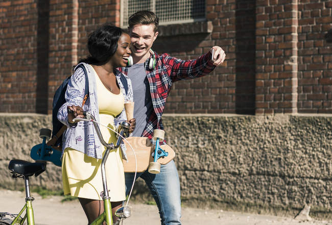 Couple with bicycle and skateboard taking selfies — Stock Photo