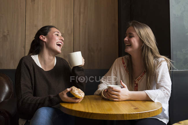 Friends with coffee cups in cafe — Stock Photo
