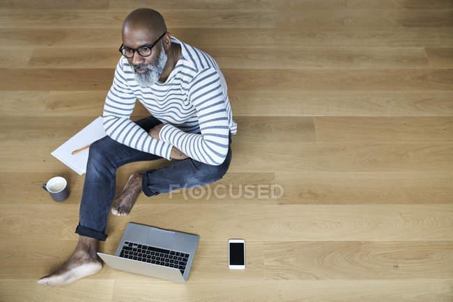 Портрет зрілою людиною, сидячи на підлозі — стокове фото