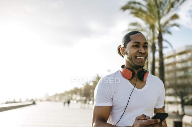 Hombre con auriculares y teléfono celular en la playa - foto de stock