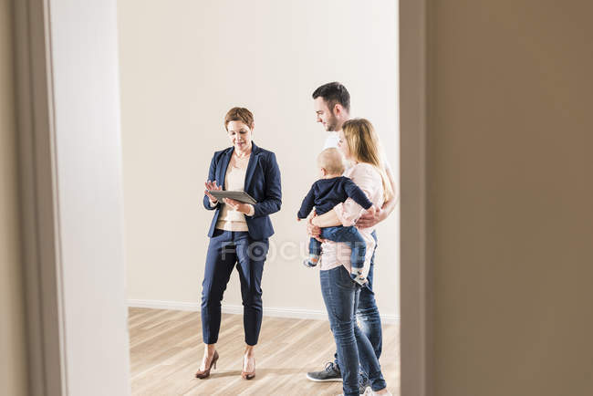 Real estate agent and family using tablet indoors — Stock Photo