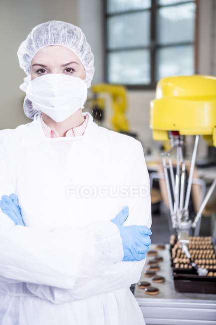 Portrait of woman in protective workwear with robot handling cookies in background — Stock Photo