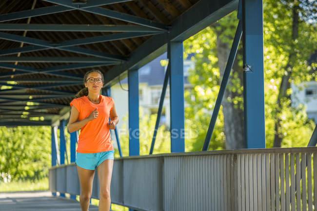 Молодая женщина бежит по мосту — стоковое фото