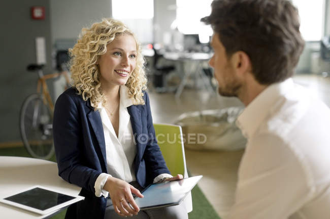 Businessman and woman discussing project in office, using digital tablet — Stock Photo
