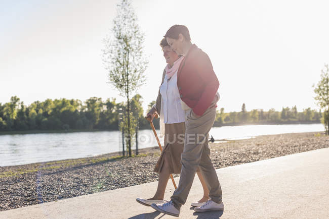 Woman and daughter strolling near river — Stock Photo
