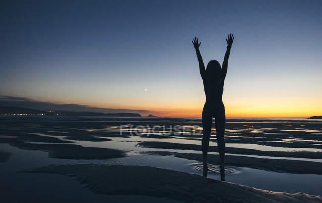 Молода жінка, стоячи з підняв руки морем на заході сонця — стокове фото