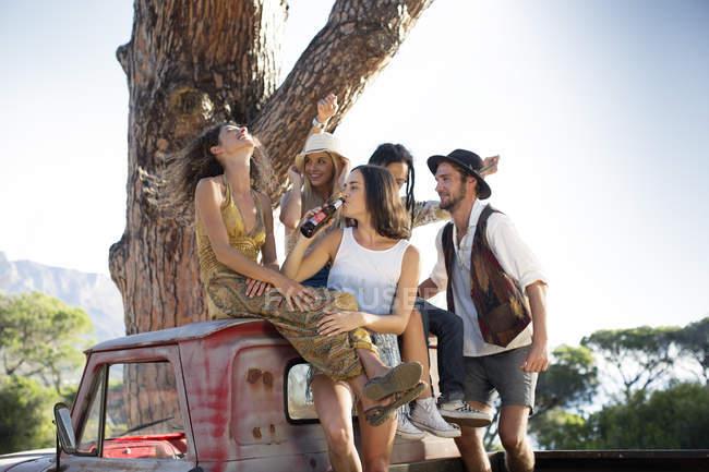 Jeunes heureux assis près de van et de s'amuser — Photo de stock