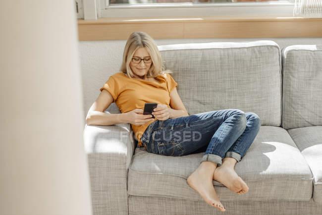 Frau auf Couch mit Handy — Stockfoto