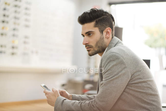Young man holding smartphone in shop — Stock Photo