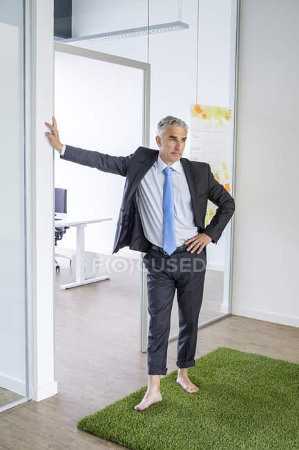 Homme d'affaires debout pieds nus sur tapis d'herbe — Photo de stock