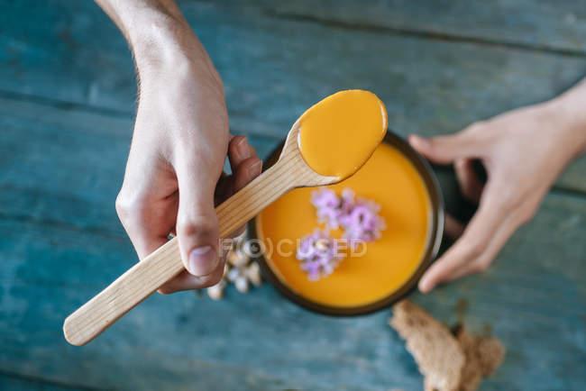 Mãos de macho comendo sopa de abóbora com natas — Fotografia de Stock
