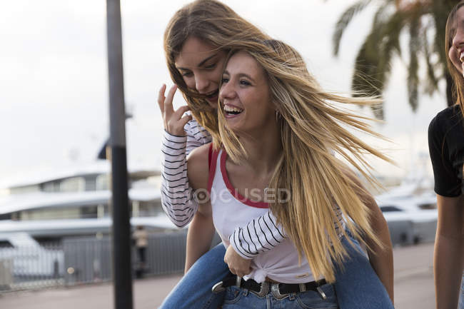 Woman giving her friend a piggyback ride — Stock Photo
