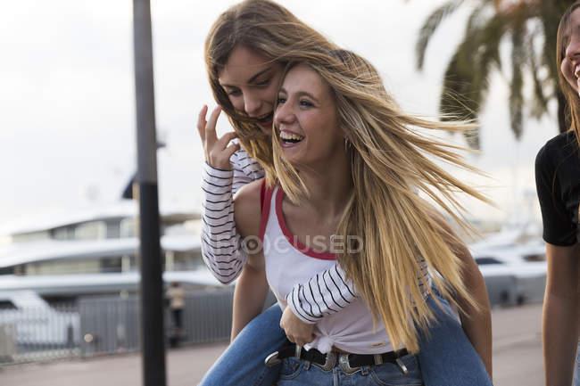 Geben ihrer Freundin eine Huckepack Fahrt Frau — Stockfoto