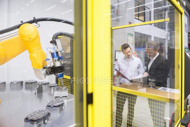 Hombres de negocios observando robot industrial - foto de stock