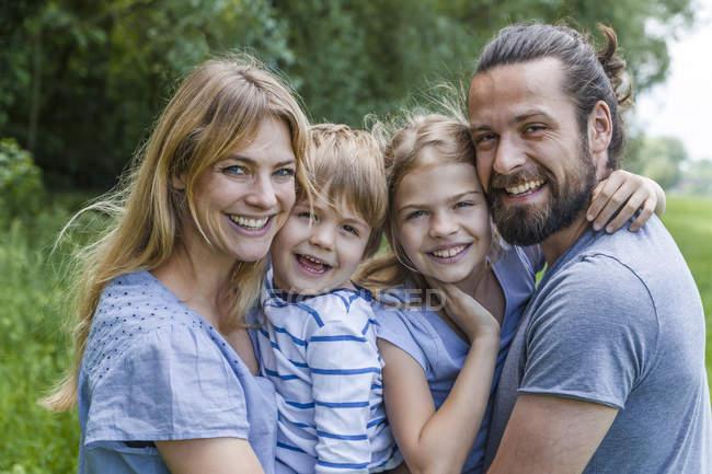 Família feliz em pé na natureza — Fotografia de Stock
