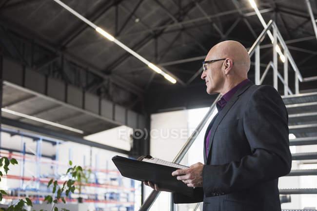 Homme d'affaires debout avec des documents — Photo de stock