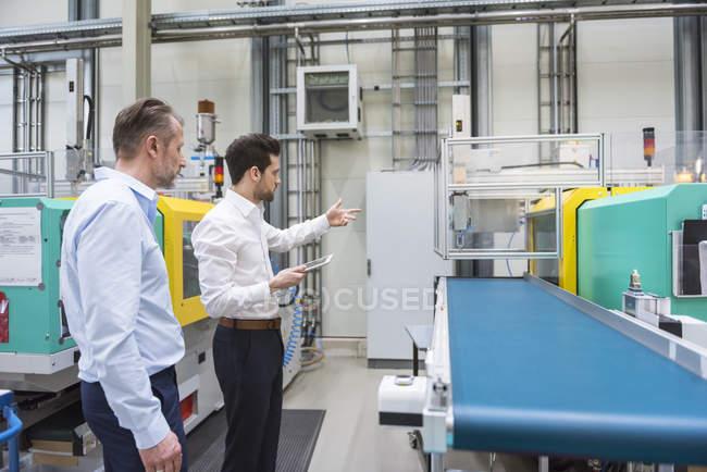 Men examining machine — Stock Photo