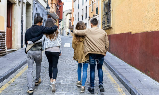 Two couples strolling on street — Stock Photo