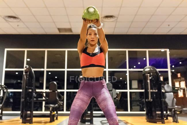 Woman lifting kettlebell — Stock Photo