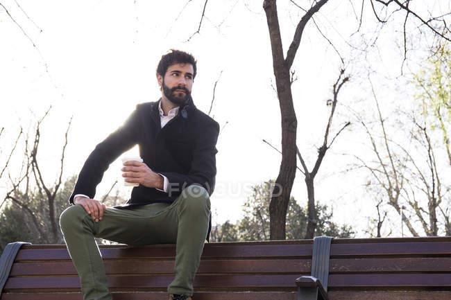 Homem sentado no encosto do banco — Fotografia de Stock