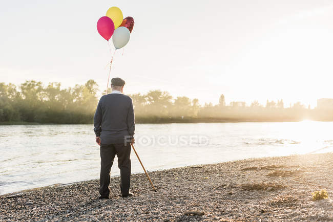 Senior man with balloons standing at riverside — Stock Photo