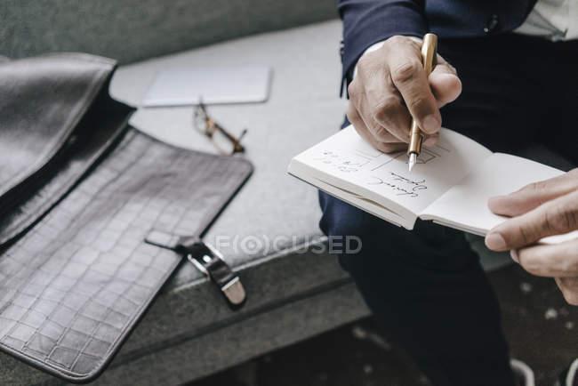 Бізнесмен пише в зошиті — стокове фото