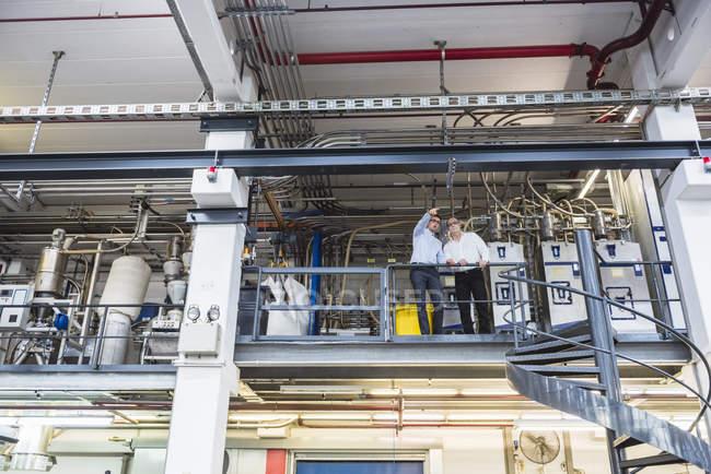 Men standing in factory shop floor — Stock Photo
