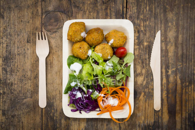 Falafel and salad on disposable plate — Stock Photo